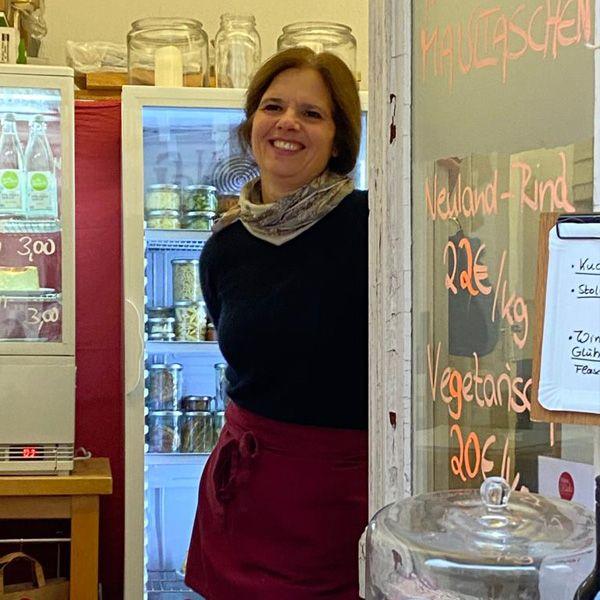 Steffi steht an der Vitrine am Fensterverkauf
